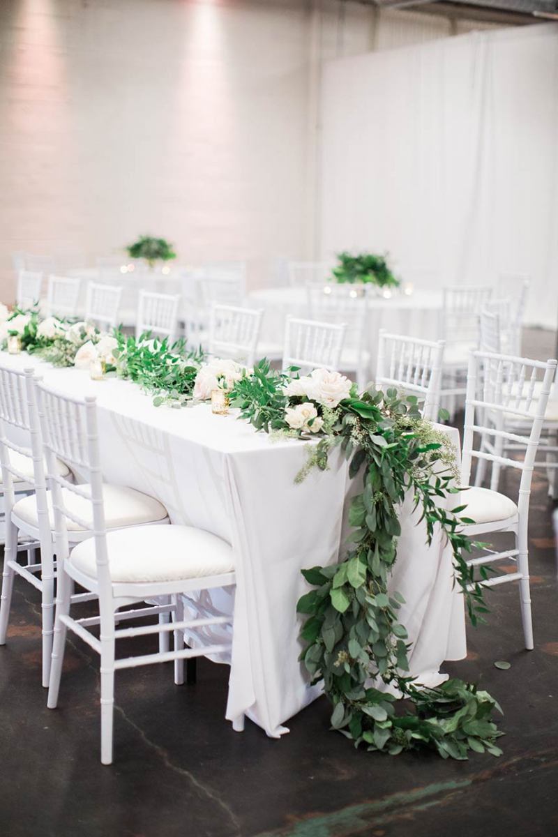 All White Tables and Chairs with Green Garland on Reception Tables