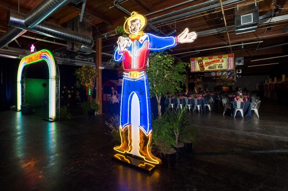 A large neon sign of Big Tex in event space.