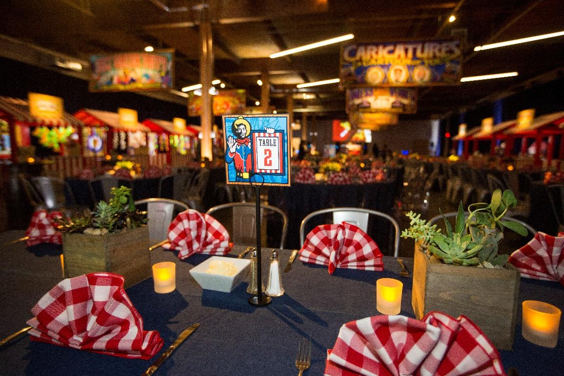 Table showcasing a Big Tex-themed table card and hand placed napkins.